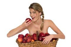 Junge blonde Frau, die einen Bissen eines roten Apfels nimmt Lizenzfreie Stockbilder