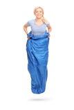 Junge blonde Frau, die in einen blauen Sack springt Lizenzfreies Stockbild