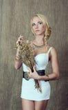 Junge blonde Frau, die einen Blumenstrauß von dekorativem hält Stockbilder