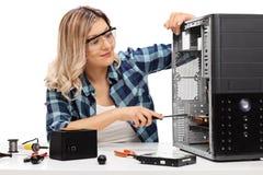 Junge blonde Frau, die einen Computer repariert Lizenzfreies Stockbild
