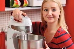 Junge blonde Frau, die einen Mischer in der roten Küche verwendet. Lizenzfreie Stockfotos