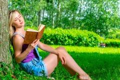 Junge blonde Frau, die einen Roman im Park liest Stockfotos