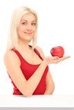 Junge blonde Frau, die einen roten Apfel anhält Lizenzfreie Stockfotos