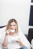 Junge blonde Frau, die einen Tasse Kaffee genießt Stockfotos