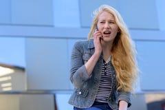 Junge blonde Frau, die einen Telefonanruf macht Stockfoto