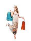 Junge blonde Frau, die Einkaufstaschen hält Stockfotografie