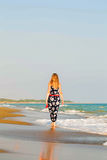 Junge blonde Frau, die entlang den Strand geht Stockbilder