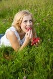 Junge blonde Frau, die Erdbeeren isst Stockfotos