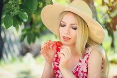 Junge blonde Frau, die Erdbeeren am sonnigen Tag des Gartensommers, den warmen Sommer Bild tonend, die Selbsthilfe und den gesund Stockfotos