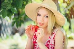 Junge blonde Frau, die Erdbeeren am sonnigen Tag des Gartensommers, den warmen Sommer Bild tonend, die Selbsthilfe und den gesund Lizenzfreie Stockbilder