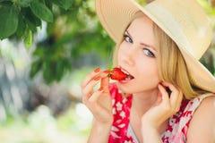 Junge blonde Frau, die Erdbeeren am sonnigen Tag des Gartensommers, den warmen Sommer Bild tonend, die Selbsthilfe und den gesund Lizenzfreie Stockfotos