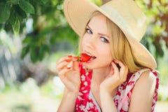 Junge blonde Frau, die Erdbeeren am sonnigen Tag des Gartensommers, den warmen Sommer Bild tonend, die Selbsthilfe und den gesund Stockfoto