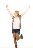 Junge blonde Frau, die für Freude springt Stockbild