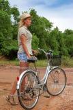 Junge blonde Frau, die Fahrrad in der Landschaft fährt Lizenzfreies Stockbild