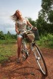 Junge blonde Frau, die Fahrrad in der Landschaft fährt Stockfoto