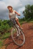 Junge blonde Frau, die Fahrrad in der Landschaft fährt Stockbild
