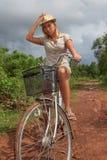 Junge blonde Frau, die Fahrrad in der Landschaft fährt Stockfotos