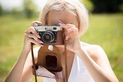 Junge blonde Frau, die Fotoschüsse durch Weinlesekamera macht Lizenzfreies Stockfoto
