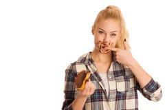 Junge blonde Frau, die Frühstücksbrot- und -nugatverbreitung isola isst Lizenzfreies Stockfoto
