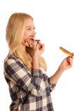 Junge blonde Frau, die Frühstücksbrot- und -nugatverbreitung isola isst Stockfotografie