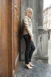 Junge blonde Frau, die gegen eine Tür steht Stockbilder