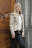Junge blonde Frau, die gegen eine Tür steht Stockfoto