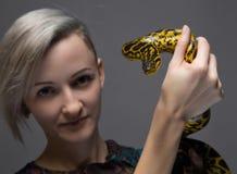 Junge blonde Frau, die gelbe Anakonda hält Stockfotografie