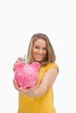 Junge blonde Frau, die Geld in eine Piggyquerneigung steckt Lizenzfreie Stockbilder