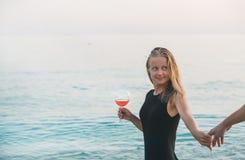 Junge blonde Frau, die Glas der Hand des rosafarbenen Weins und des Mannes auf Strand durch das Meer bei Sonnenuntergang hält Ala Lizenzfreies Stockbild