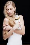 Junge blonde Frau, die Glas Weißwein hält Stockfoto