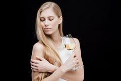 Junge blonde Frau, die Glas Weißwein hält Lizenzfreies Stockbild