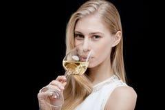 Junge blonde Frau, die Glas Weißwein hält Stockfotos