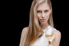 Junge blonde Frau, die Glas Weißwein hält Lizenzfreies Stockfoto