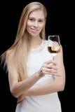 Junge blonde Frau, die Glas Weißwein hält Lizenzfreie Stockfotografie