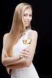 Junge blonde Frau, die Glas Weißwein hält Stockbilder
