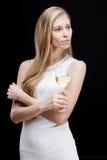 Junge blonde Frau, die Glas Weißwein hält Lizenzfreie Stockfotos