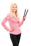 Junge blonde Frau, die Haarstrecker hält Lizenzfreies Stockfoto