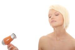 Junge blonde Frau, die Haartrockner verwendet Stockbilder