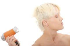 Junge blonde Frau, die Haartrockner verwendet Lizenzfreies Stockfoto