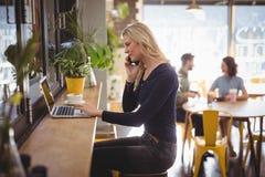 Junge blonde Frau, die am Handy bei der Anwendung des Laptops spricht Stockfotografie