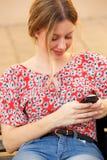 Junge blonde Frau, die Handy betrachtet Lizenzfreies Stockfoto