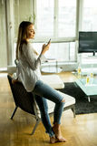 Junge blonde Frau, die Handy betrachtet Stockfotografie