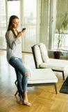 Junge blonde Frau, die Handy betrachtet Stockbild