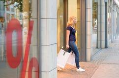 Junge blonde Frau, die heraus in der Stadt kauft Lizenzfreie Stockfotos