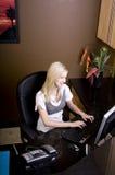Junge blonde Frau, die hinter Schreibtisch arbeitet Stockbild