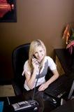 Junge blonde Frau, die hinter Schreibtisch arbeitet Stockfotos