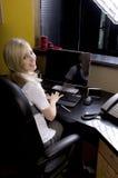 Junge blonde Frau, die hinter Schreibtisch arbeitet Lizenzfreie Stockfotos