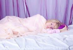 Junge blonde Frau, die in ihr Bett legt Stockbilder