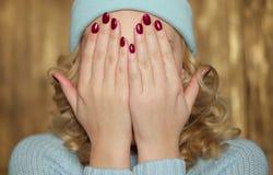 Junge blonde Frau, die ihr Gesicht bedeckt Lizenzfreies Stockfoto