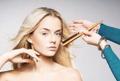 Junge blonde Frau, die ihr Haar angeredet erhält Stockbilder